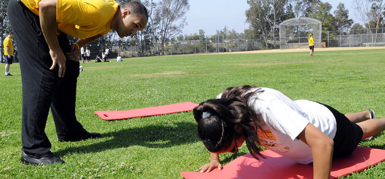 110622-N-CW427-027 SAN DIEGO (June 22, 2011) Culinary Specialist 3rd Class Kyle Fearno, assigned to Naval Medical Center San Diego, cheers a middle school student to finish her push-ups during a physical fitness field day at Jean Farb Middle School. Members of the medical center staff volunteered to lead more than 650 middle school students in various physical activities, such as obstacle courses, relay races and a tug-of-war. (U.S. Navy photo by Mass Communication Specialist Seaman Clay M. Whaley/Released)